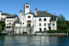 People rowing on a canoe in front of San Giulio island Royalty Free Stock Photography