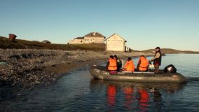 People in rubber boat on background of abandoned houses New Earth Vaigach. stock video footage