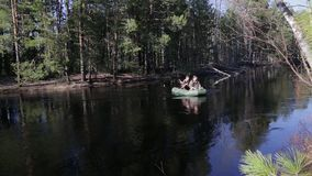 People in a rubber boat floating. Down the fast current of the taiga river stock video footage