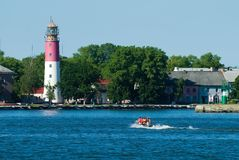 People in rubber boat and lighthouse is Baltiysk Royalty Free Stock Images
