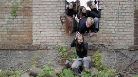 People at ruins concepts of fear. Concepts of fear. Group of young people in a hole in the wall of the post of the apocalypse on the ground. Young people in stock video footage