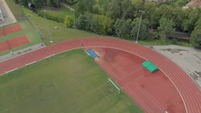 People run in the red stadium fitness. Sports field and red stadium, running, flying on a drone 4k stock video