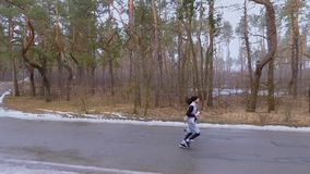 People running along road in the forest. Young sport people makes morning exercises outdoors. Pretty woman and handsome man wearing sportswear runs in the forest stock video footage
