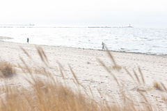 People running on the beach with waves and lighthouse in the ear Stock Images