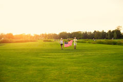 People running and carrying flag. Stock Photography