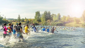 People running into a lake Stock Images