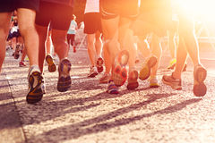 People running marathon. Marathon running race people competing in fitness and healthy active lifestyle feet on road Stock Image