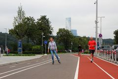 People running and rollerblading along a dedicated strip Stock Images