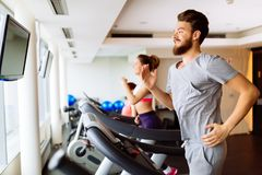 People running on treadmill in gym. Doing cardio workout Stock Photos