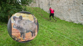 People running uphill and passing a target. Slow motion video in Raw of people running uphill and passing a target stock video footage