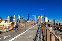 People running and walking on Brooklyn bridge with Manhattan skyline view. USA stock image