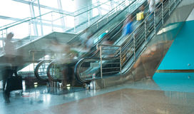 People rush on escalator motion blurred. In the airport Stock Photos