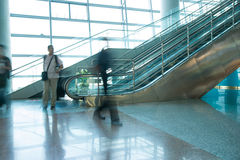 People rush on escalator motion blurred. In airport Stock Photography