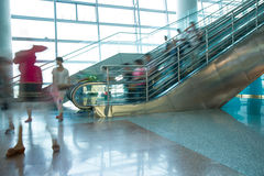 People rush on escalator motion blurred. In airport Stock Images