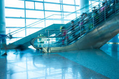 People rush on escalator motion blurred. In the airport Royalty Free Stock Image