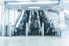 People rush on a escalator motion blurred. Blue white balance processing style Royalty Free Stock Photos
