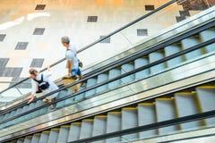 People rush on escalator motion blurred Stock Image
