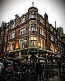 People rush by London Pub exterior in evening light at Covent Garden. People rush by a pub in Covent Garden in pouring rain, London Great Britain in evening Stock Photos