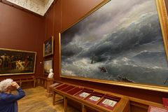 People of Russian Museum in St. Petersburg, Russia. St. Petersburg, Russia - April 24, 2017: Visitor at the painting of Ivan Aivazovsky in the Russian Museum. It Stock Images