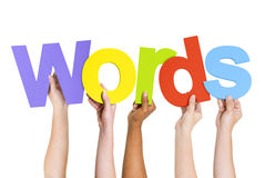 People's Arms Raised Holding Word Words. Multi-Ethnic Group Of People's Arms Raised Holding Letters That Form Words stock photo