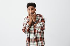 People`s emotions. Portrait of frightened dark-skinned attractive african men with curly hair in casual shirt gnawing Royalty Free Stock Photography