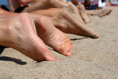 People's feet on a beach. Stock Photo