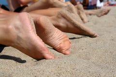 People's feet on a beach. stock photo