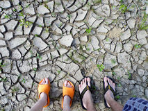 People's feet on the ground cracked soil. In the forest Royalty Free Stock Images