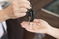 people's hand give and get car key with car background Stock Image