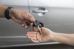 people's hand give and get car key with car background Stock Images
