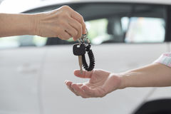 people's hand give and get car key with car background Royalty Free Stock Images