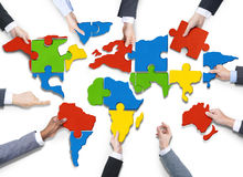 People s Hands with Jigsaw Forming in World Map. Group of Business People with Jigsaw Puzzle Forming in World Map Stock Image