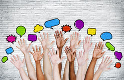 People's Hands Raised with Speech Bubbles Stock Image
