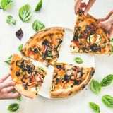 People`s hands taking Freshly baked vegetarian pizza over marble background stock photos
