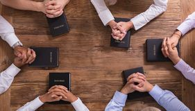 People`s Praying Hands On Holy Bible. High Angle View Of People`s Praying Hands On Holy Bible royalty free stock images