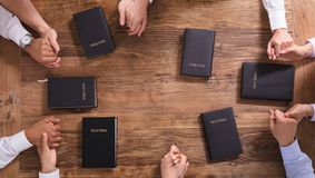 People`s Praying Hands On Holy Bible. High Angle View Of People`s Praying Hands On Holy Bible royalty free stock photography
