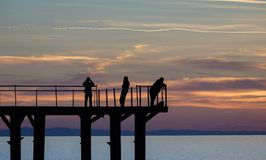 People`s silhouettes on the pier. Shooting fishing and talking on the phone silhouettes on the pier, cloudy sunset background Stock Photography