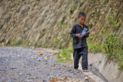 People of Sa Pa in Vietnam. Young boy of the Black Hmong ethic minority people is walking on the road  in the mountains of Sa Pa Royalty Free Stock Image