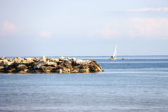 People sail on a sailboat on calm sea royalty free stock photography