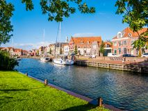 People and sailboats in old harbour of historic town of Enkhuizen, Noord-Holland, Netherlands. People and sailing boats in old harbour of historic town of stock photo
