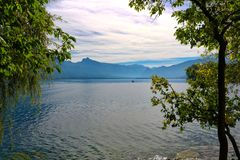 People are sailing the lake surrounded by mountains royalty free stock images