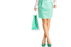 People, sale, black friday concept - woman with shopping bags. People, sale, black friday concept -  woman in green skirt with shopping bag isolated on white Royalty Free Stock Photo