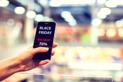 People, sale, consumerism, advertisement concept - close up of w. Oman`s hand holding shopping bags and smartphone with black friday inscription royalty free stock photo