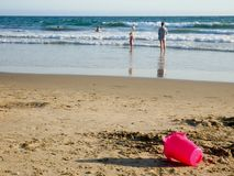 People in a sandy beach sea shore and a pink plastic bucket on the foreground royalty free stock images