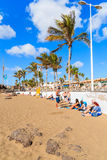 People on sandy tropical beach with palm trees Stock Images
