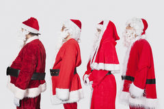 People in Santa costume standing in row against gray background Stock Images