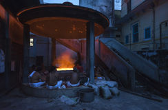 Hindu people sit around fire at night Stock Photo