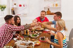 People say cheers clink glasses at festive table dinner party. Group of people clink glasses, saying cheers, eat healthy meals at party dinner table in cafe Stock Photos