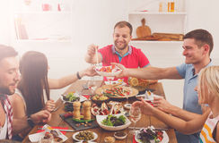 People say cheers clink glasses at festive table dinner party Stock Images