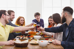 People say cheers clink glasses at festive table dinner party. Group of people clink glasses, saying cheers, eat healthy meals at party dinner table in cafe Royalty Free Stock Photography